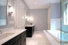 Blue gray elegant bathroom! black bathroom cabinets, chrome bathroom mirrors, chrome modern sconces, white carrara carrera marble bathroom countertops, chrome faucets, white marble tiles floors and crisp white crown molding! black blue gray white bathroom colors.