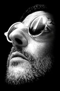 Jean Reno Extreme closeup. Butterfly, face turned up and at angle. Glare on glasses displays a tall building. Background is burned out? Emphasis on nose, facial hair and lips-the actor's trademarks.  Love The Professional!