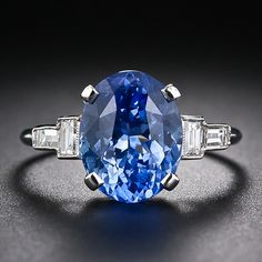 An entrancing electric cornflower blue Ceylon sapphire, weighing 4.78 carats, is elegantly presented in a classic Art Deco mounting, hand crafted in platinum, between a pair of perpendicularly arranged, bright-white baguette diamonds