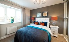 Orange and turquoise double bedroom with white cushioned headboard.