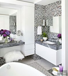 The simple styling of high-gloss lacquered cabinetry balances dramatic tilework on the floor and walls of this black-and-white bathroom. Polished marble counters with a mitered edge give the heafty appearance of extra-thick slabs, while a serene egg-shape tub stands out against the busy tile patterns.