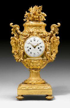 "c1800 IMPORTANT VASE CLOCK ""A TETES DE BELIER"",Louis XVI, the dial signed CORNIQUET A CHAILLOT (Philippe Jacques Corniquet, maitre 1785), Paris circa 1800. Matte and polished gilt bronze. Enamel dial and 2 fine gilt hands. Anchor escapement striking the 1/2 hours on bell. Rich gilt mounts and applications H 76 cm. Sold for CHF 30 000 (hammer price)"
