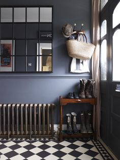 Dark hallway interiors with inky blue walls, a cast iron radiator and window pane wall mirror. Compact shoe storage for hallway. Also, I'd forgotten how much I LOVE chequered floors.