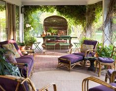 Matching Sunbrella upholstery and a round indoor-outdoor rug from Couristan unify an assortment of vintage rattan porch furniture into an open-air living room suite. Behind the chaise longue, a grand hooded basket chair — handed down and restored for generations — presides over a massive table and lightweight French park chairs.   - HouseBeautiful.com