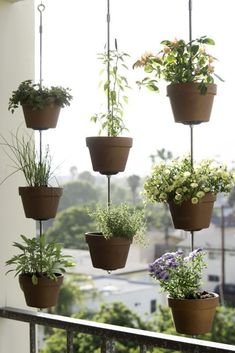 Make a DIY vertical garden that easily fits in an apartment balcony or small backyard! This space saving garden uses ropes, a few cuts of wood and clay garden pots to display and hang flowers, herb or vegetables. We give you directions to make this DIY outdoors project and suggest plants to pot in the clay containers. #verticalvegetablegardens #smallherbgardens