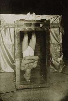 harry houdini upside down in a water torture cell. 1912.