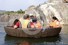 A tourist family on a coracle ride in the deep canyons  though which Cauvery River flows,  at Hogenakkal Falls, Tamil Nadu.