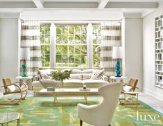 The light-flooded living room is the most formal entertaining space, all-white except for a bold green rug that serves as a grounding element for the stylish modern furnishings, including 1930s French cantilevered chairs, swooping '50s armchairs from Sweden, and a Nahem-designed sofa with cane detailing.