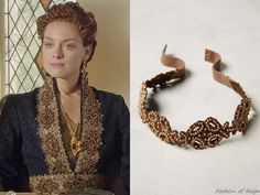 """In the episode 3x06 (""""Fight or Flight"""") Queen Elizabeth wears the lavishReign Costumes Custom Black & Gold Coat Dress. The golden lace trim of Elizabeth's costume was embellished with this Anthropologie Pearl Vineyard Belt (used as an appliqué).Worn with the VSA Designs earrings."""