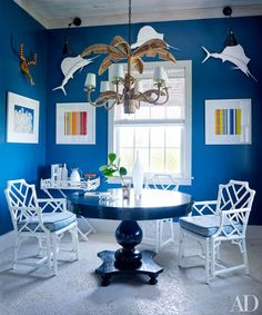 Painted in a Benjamin Moore blue, the card room in Alessandra Branca's Bahamas getaway includes photographs by Tema Stauffer (left) and Jonathan Lewis and a table by Jayson Home