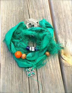 recycled sari ribbon adorned with a repurposed silver and green charm, silver beads, wood beads, blue glass tube beads, and an orange glass bead. #hippsieloveshop #etsy