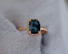 Teal sapphire ring. Rose gold engagement ring. Engagement ring by Eidelprecious. This ring features a 4.5ct cushion sapphire. The color is gorgeous deep peacock green with blue flashes. The sapphire is very beautiful and clean. This beauty is set in Eidelprecious Blake setting 14k rose gold diamond