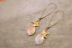 Flat pearl earrings are made with a flat coin pearl bead and a gold bird charm and hang on a kidney earring hook.