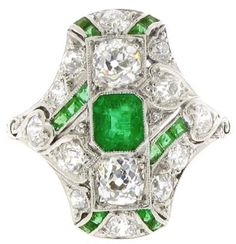 Emerald and diamond ring. Ornate cluster ring, set to centre with an octagonal emerald in a rub over setting with an approximate weight of 0.50ct. Set throughout with fourteen old cut diamonds with an approximate total weight of 1.50ct. Calibré emeralds set in a criss cross pattern across the ring, with an approximate total weight of 0.70ct. All to an ornate shank and cheniered gallery. Mounted and set in platinum, circa 1910. Berganza.