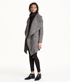 Double-breasted coat in mélange, wool-blend bouclé yarn. Wide shawl collar, concealed snap fasteners at front, side pockets, and one inner pocket. Asymmetric hem. Tab at back. Lined.