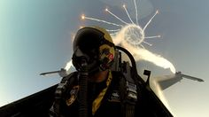 F-16 diving and rolling while firing flares.