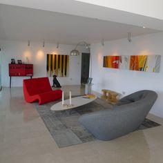Se escogieron  piezas de mobiliario bajas para resaltar la continuidad con el horizonte. Los tonos claros del piso de  mármol Boticino y las paredes pintadas  en blanco permiten el contraste con la vista y con las obras expuestas