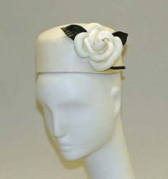 Pillbox Hat- A pillbox hat features a flat crown and straight sides with no brim. It was originally a military style hat, but was popularized by Jackie Kennedy. This hat was made by Balenciaga.
