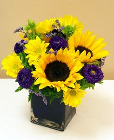 Sunny Day-Send a gift that will make them smile. This arrangement is designed in a purple cube and filled with sunny sunflowers, yellow daisies and purple accent flowers. #CasasAdobesFlowerShop #TucsonFlowers #MardiGras #MardiGrasFlowers