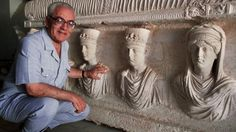 """Syrian archaeologist killed in Palmyra by IS militants because he refused to reveal the location of key artifacts. He is now hanging, beheaded, from a light post. A sign attached to the body accused him of being an apostate who was in regular communication with and supported the government of Syrian President Bashar al-Assad. He was also accused of representing Syria at overseas conferences with """"infidels"""", in addition to being director of Palmyra's """"idols"""". 