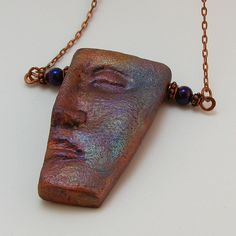 Raku-Style Polymer Clay Pendant - technique used by Mary Schultz aka Artistical Girl on Flickr. She used interference paints and also added a texture paint layer on top of the polymer clay. She then added accents of copper paint and mica powders.