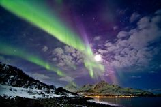 """""""Moonlight and Auroras"""" - This image from March 11th, 2011, shows the small village of Tromvik on Kvaløya Island. This is just a short drive from the city of Tromsoe, Norway. The full moon shines on the rocks & sea. To the west the Aurora waves runs across the sky. - Copyright : Frank Olsen"""