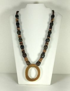 This vintage necklace is made of wood beads and a lucite pendant. Perfect for…