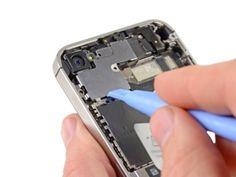 STAP 3  Gebruik de rand van een plastic openingstool om de klemmetjes van het beschermkapje van de kabel los te maken van hun sleuven in de EMI-afscherming op het logic board.