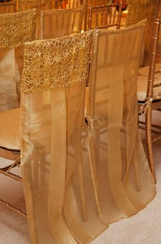 Sheer organza allows guests to view the luxurious gilded chairs underneath.