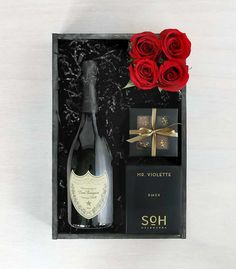 A bottle of fine champagne pairs with a quartet of truffles from Chocolate Therapy alongside a pavé of svelte red roses: 'Champagne & Candlelight' by Winston Flowers.