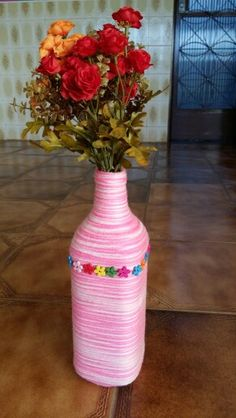 Juice bottle decored with thread and little wood flowers.