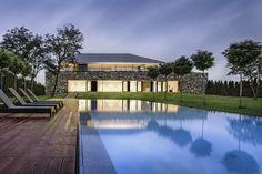 Vue de nuit depuis la piscine située au fond du jardin de cette belle maison d'architecte