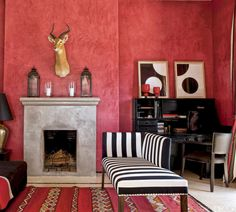 In a Moroccan vacation home, the salon walls are coated with a striking red stucco and a taxidermy antelope hangs above a fireplace covered in tadelakt, a traditional Moroccan plaster technique. The chaise is upholstered in a striped fabric from Toiles de Mayenne, and silk-screened prints by Gerhard Doehler sit above the desk.