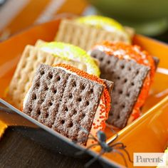 To make these colorful treats, spread 4 graham cracker squares with chocolate-hazelnut spread and 4 graham cracker squares with marshmallow crème. Pair off the chocolate covered and marshmallow covered cracker squares and sandwich them together. Place on a microwave-safe plate and microwave, uncovered, on high for 30 seconds. Sprinkle the gooey edges in colorful orange, yellow, and black nonpareils.