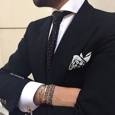 Black suit, silk polka-dot tie; silk, patterned kerchief; assorted bracelets, cufflinks... I mean,...does it get cooler than this?
