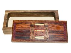 Handmade box by Jeffrey Seaton with a lid of cocobolo, maple, purple heart, walnut, black and white ebony, satine, cumaru, Hawaiian koa, eucalyptus burl. The body is made from walnut and is 1 1/2″D. Each box is completely handmade using rare and exotic woods. Each is created spontaneously and no two are ever exactly alike. Each is sanded seven times to a satin smooth surface and finished in an oil and wax finish. Size: 10 3/4″L x 4 7/8″D x 2 1/2″H Price: $380.00  -- on ScrimshawGallery.com…