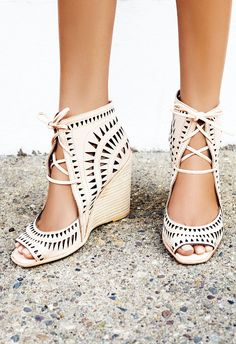Laser cut leather wedges featuring an open toe, adjustable lace-up detailing and a stacked wedge. Padded footbed for extra comfort. Rubber sole.