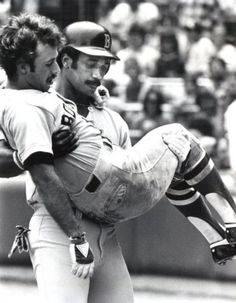 Red Sox player Jim Rice carries an injured Jerry Remy off the field to the clubhouse. Circa 1978.