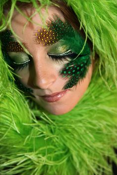 Crystal lined eye lashes accent green shimmery eye shadow enhanced with feathers.