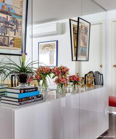 Buffet de laca cinza na sala de jantar com livros, flores e quadros ao redor compondo a decoração