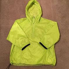 Nike nylon pullover NWOT Nike neon lime green 100% nylon pullover with attached hood. 3/4 sleeve trimmed in black, Pouch front pockets, drawstring bottom, 1/2 zipper opening, back zipper pocket.  Size large.  $28 Nike Jackets & Coats