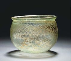 "A LATE ROMAN GREEN GLASS INSCRIBED BOWL  4TH CENTURY A.D.  The bulbous bowl with folded slightly flaring rim, the body decorated with wheel-cut wide band of cross-hatching above the double-line Greek inscription ""YTIA"" (Good Health)  2½ in. (6.4 cm.) high; 3¼ in. (8.2 cm.) rim diam."