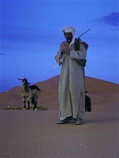 A Moroccan goat herder in the desert keeping busy doing his job- watching over the goats.