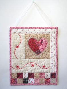 This adorable mini quilted wall hanging is the perfect touch for any shabby cottage chic room! This little quilt was inspired by vintage crazy quilts. I started with a collection of new, vintage, and upcycled fabrics, all with a shabby chic feeling and a color scheme of red, cream, and pink. I crazy pieced the heart, then machine appliqued it with a red blanket stitch. The red flower and vine border is hand embroidered. Finally, I added a row of traditional four patches at the bottom of the…