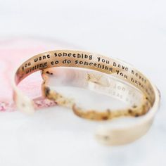 "Make a statement on your arm and set an intention in your heart with this inspirational quote bracelet. The inside of the bracelet features the quote by Thomas Jefferson, ""If you want something you have never had you must be willing to do something you have never done."" A pair of arrows are on the outside ends, pointing toward the center."