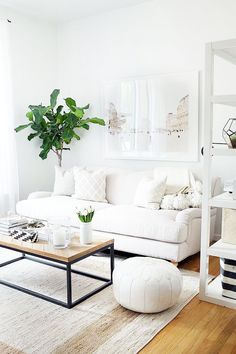Living room with white walls, white shelving unit, white couch, white artwork, patterned throw-pillows, wooden coffee table, beige rug, and plants