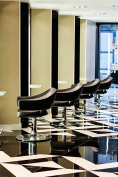 The decor of this modern elegant beauty salon creates a sense of luxury through the use of black and white tile patterns.  The interior design is sophisticated with its use of bronze sheer curtains to create private treatment rooms. Other decor ideas are the use of sleek styling stations giving a boutique hair salon ambiance. | #floor | #hair | #geometric |