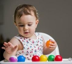 This baby is holding the balls and identifying the textures of the smooth, round balls.
