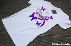 """We are inspired by this beautiful Believe Purple Ribbon Butterfly Shirts featuring the word """"Believe"""" in scripted text surrounded by butterfly designs with silhouettes of gray and a purple awareness ribbon for causes such as Alzheimers, Lupus, Pancreatic Cancer and more."""