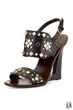 A wooden heel, hint of leather and mirror studs give a modern edge to these Tory Burch wedge sandal.